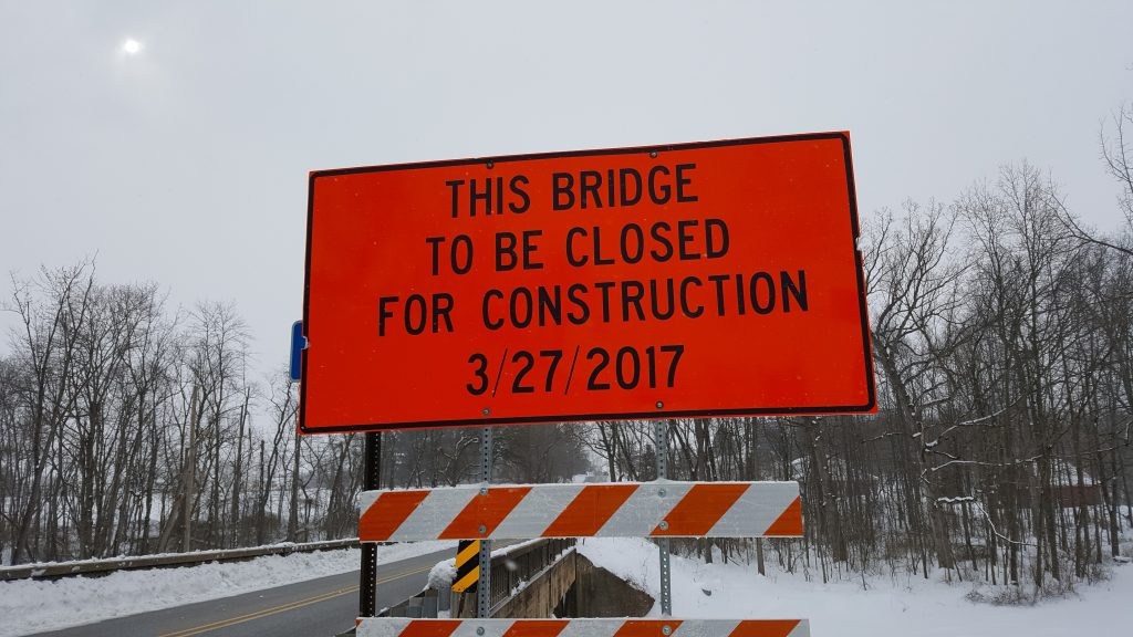 "Bright orange street sign with black text stating, ""This bridge to be closed for construction 03-27-2017"" referring to the bridge on Bull Rd by Graffius"