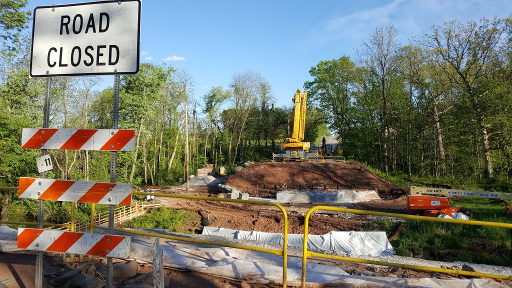 Road closed sign in foreground with a view looking south on Bull Rd. The bridge is no longer there and construction equipment is on-site.