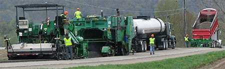 Cold-in-place road surfacing being applied by a crew wearing green shirts, blue jeans and hardhats.