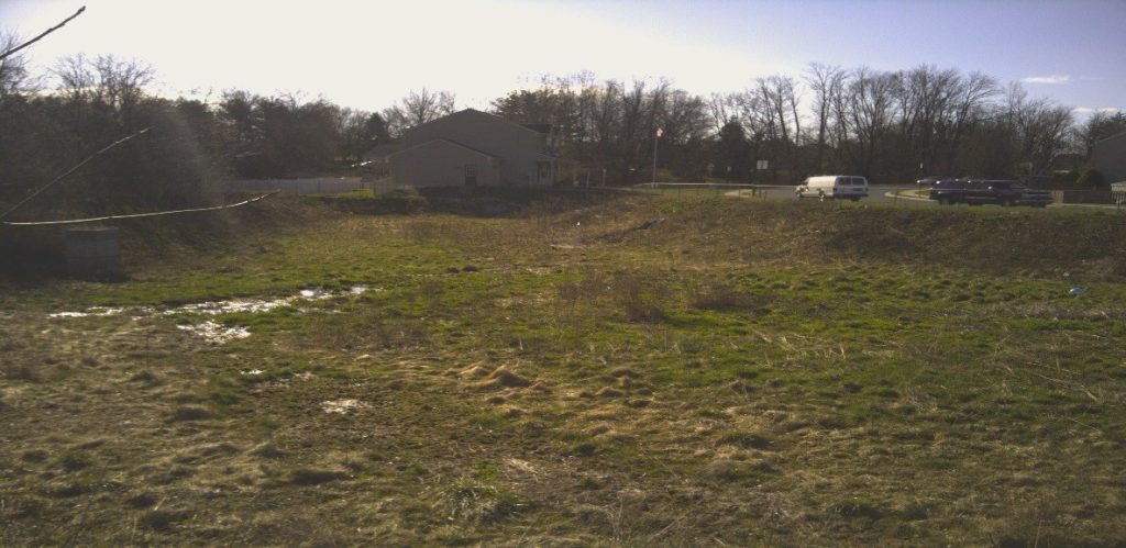 Picture of a stormwater retention pond within the Township. Grass is brownish green within the BMP and there is some standing water.