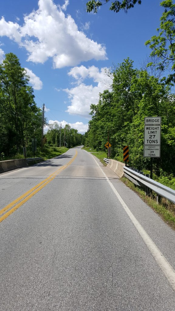 Picture of the bridge on Butter Rd between Nursery and Fox Run. There is a white Weight Restriction sign before the bridge indicating that the weight restriction for Single Vehicles is 27 tons and Combination Vehicles is 39 tons.