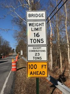 "Picture of the Weight Limit sign on Fox Run Rd. There are three white signs. The first one says ""Bridge"" the second one says ""Weight Limit 16 Tons"" the third one says ""Except combinations 23 tons."" There is also a yellow sign at the bottom that says ""100 feet ahead"""