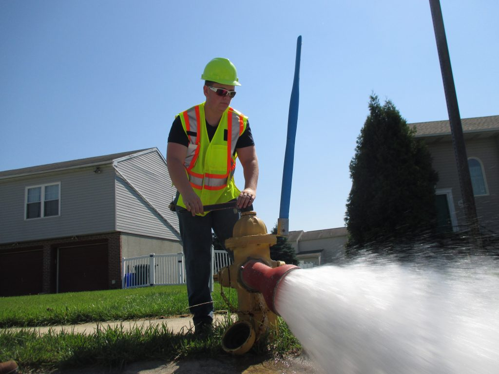 Picture of a water crew employee wearing a yellow hardhat, yellow and orange vest and blue jeans standing by a yellow fire hydrant. He is demonstrating flushing the hydrant.