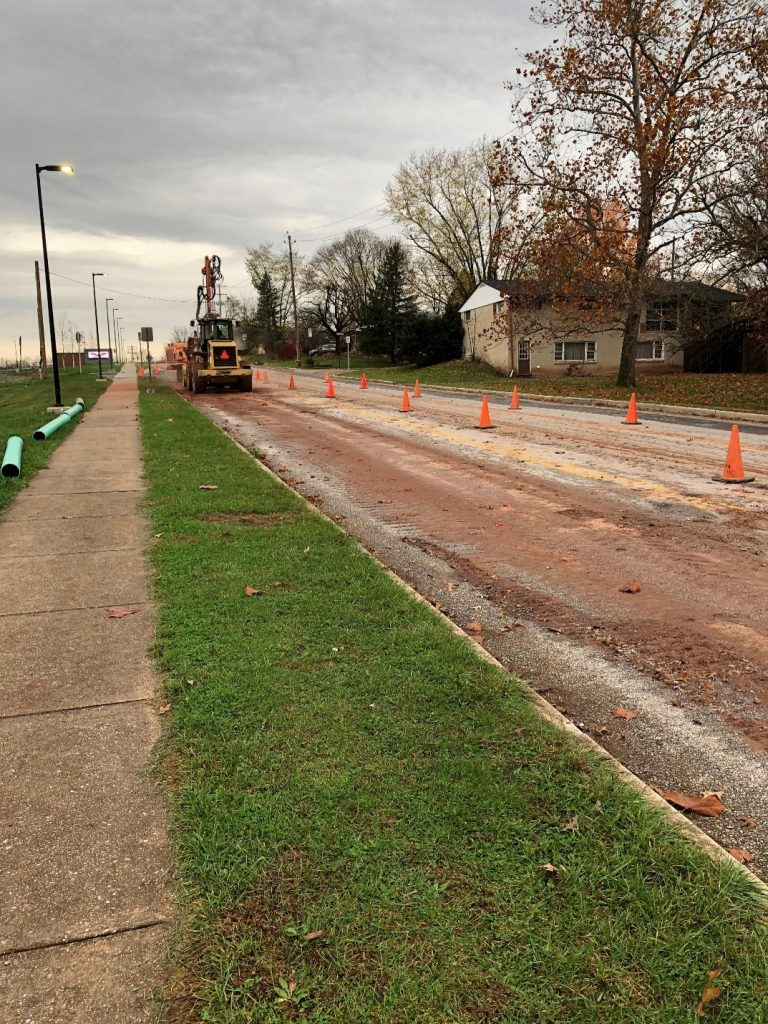 picture taken standing on the sidewalk facing up towards the new high school on Intermediate Ave. Traffic cones, sewer pipe and construction equipment are visible.