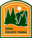 "Yellow background with green pine trees in front of a green mountain with a white sun above it. Below the trees, in green text, ""York County Parks"""