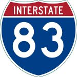 "Picture of an Interstate sign shaped like a crest. Top part is in red with white text, ""INTERSTATE"". The bottom part is blue with white text, ""83""."