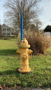 faded yellow fire hydrant with chipping paint and rust visible. A blue plastic delineator is attached to the fire hydrant. The hydrant is sitting on a green grass lawn.