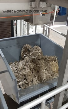 a picture of the new trash screen located within the new headworks building along with a bin of brown washed and compacted screenings